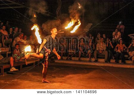 Chiang Mai, Thailand - July 24, 2011: Fire eater performs in a shows at outside the Kantoke Palace in oper air place