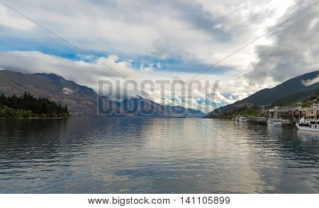 Lake view from harbour in New Zealand looking out to mountains and boats