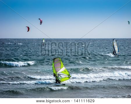 Tenerife, Canary Islands, Spain - December 22, 2008: A group of guys make kitesuifing and windsurf on waves of the Atlantic, at El Medano beach
