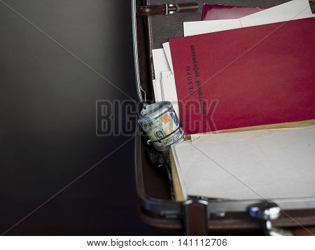 An open briefcase with a looking retro red folder and text Operative Information Review in russian concept of top secrets cropped studio shot