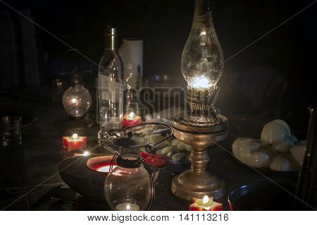 A kerosene lamp in focus and candles around the table with some food and drinks left night scene concept of blackout