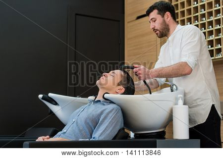 Young man at hairdresser salon getting his hair washed.