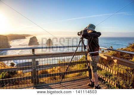 Nature australian photographer taking pictures at sunset With His tripod and wide angle chamber to the Twelve Apostles in the state of Victoria in Australia.