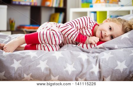 Cute little girl in pajama sleeping in bed poster