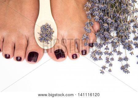 Closeup photo of a female feet with pedicure on nails and lavender. at spa salon. Legs care concept. poster