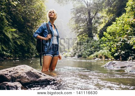 Outdoor shot of attractive young woman with backpack standing in a wilderness stream. Caucasian female hiker in creek water.