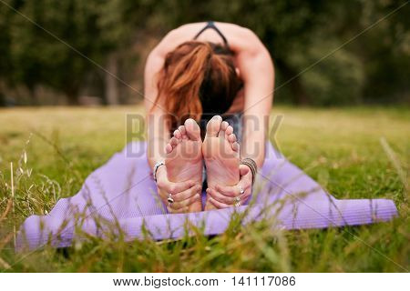 Young Woman Doing Yoga Outdoors On Grass