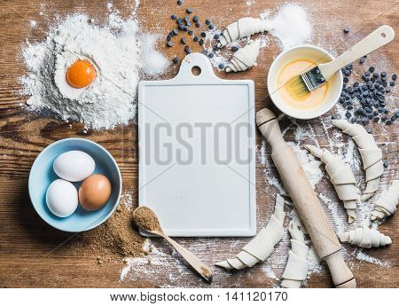 Baking ingredients for cooking croissants. Eggs, brown sugar, melted butter, flour, chocolate chips with white ceramic board in center over rustic wooden background. Top view, copy space