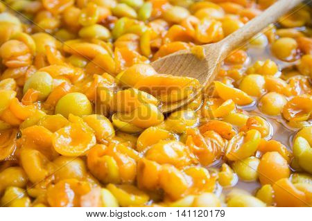 jam apricot. halves apricot in syrup. the process of making confiture.