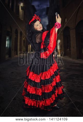 Flamenco dancer holds her mobile phone high above her head and takes selfie. Mature woman wears red and black flamenco floor-length gown with frills