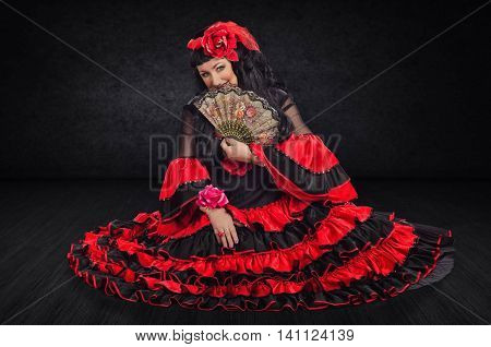 Mature woman in traditional flamenco dress seated on stage floor closes part of her face with fan. She coquettishly smiles and looks at camera
