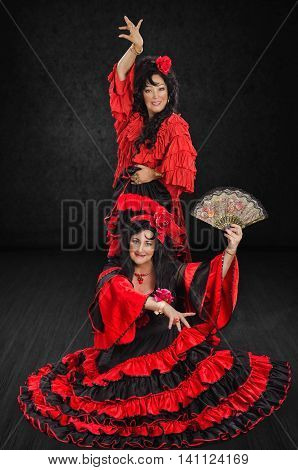 Two attractive mature women are posing in red and black flamenco style floor-length gowns with frills