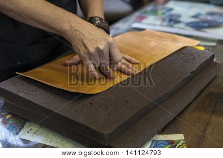 Bookbinder punching holes in leather for thread.