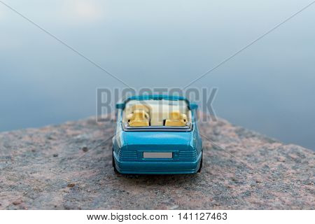 Close up image of blue convertible car standing on the edge of road
