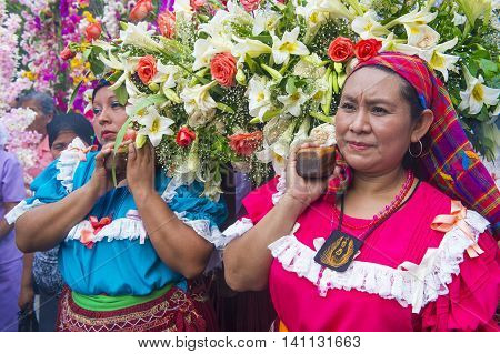 PANCHIMALCO EL SALVADOR - MAY 08 : Salvadoran woman carry an altar with a statue of Virgin Mary during the procession of the Flower & Palm Festival in Panchimalco El Salvador on May 08 2016