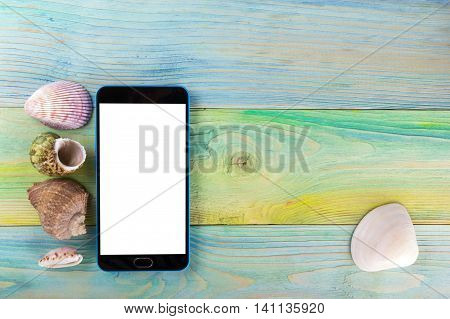 Blank screen mobile sell smartphone tablet pc. Summer sea vacation background. Notebook blank page with Travel items on blue green wooden table. Sea shells, pebbles, top view mockup