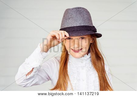 Close up portrait of pretty little girl of 8-9 years old against white wooden background. Kid wearing white vintage blouse and grey black hat