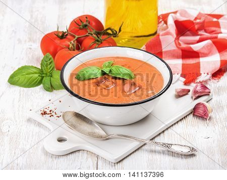 Cold gazpacho soup in bowl with ice, hot pepper and basil served with fresh tomotoes on ceramic board over white wooden background, selective focus, horizontal composition