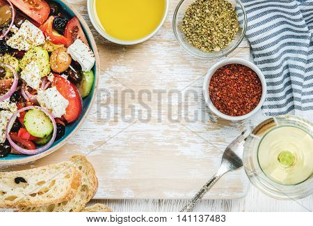 Greek salad with olive oil, bread, oregano, pepper and glass of white wine over old white painted wooden board, top view, copy space, horizontal composition