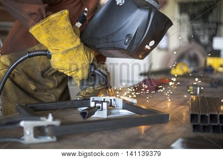 Welder welding steel stool support to each other.