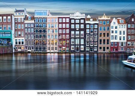 Typical house front in Amsterdam along a canal during dusk