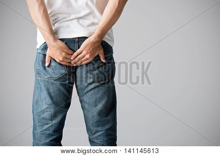 Man holding his bottom in pain isolated in grey