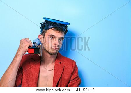 Close up of a funny young man in a red jacket with the iron  with different emotion. The collage of young man in red jacket in a swimming mask with different emotion. emotional card. misunderstanding