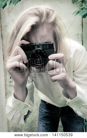 Teenager boy taking photos with old manual camera in retro style of 1970s, toned, shallow depth of field
