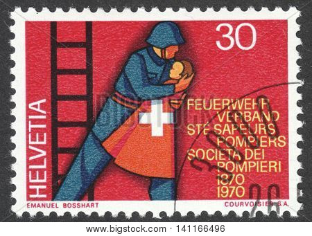 MOSCOW RUSSIA - CIRCA APRIL 2016: a post stamp printed in SWITZERLAND shows a fireman rescuing a child dedicated to the 100th anniversary of the Swiss Firemen's Association circa 1970