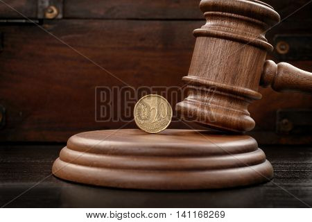 Judge gavel closeup with twenty eurocents on brown wooden background