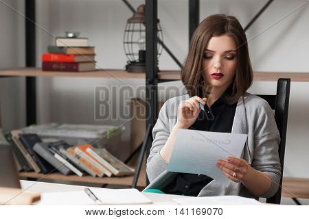 Young businesswoman working on business papers . Close up of female office manager reading papers or tax report at office
