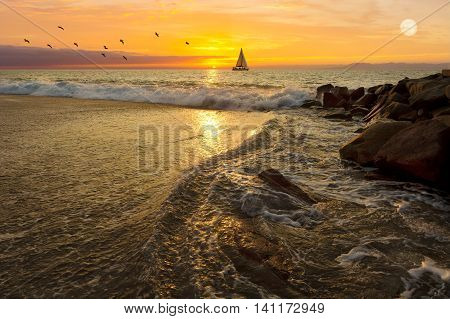 Sailboat sunset is a sailboat sailing at sea against a vivid orange sunset with a flock of birds following along as a full moon rises in the sky.