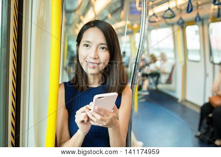 Woman using smart phone inside train compartment