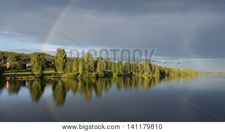 Calm river, riverside and the rainbow. Beautiful evening up North in rural County. Buildings in a village.