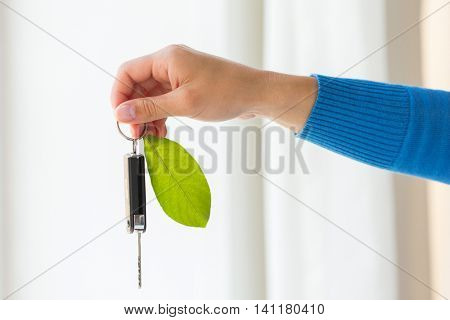 conservation, environment, people, transport and ecology concept - close up of hand holding car key with green leaf trinket