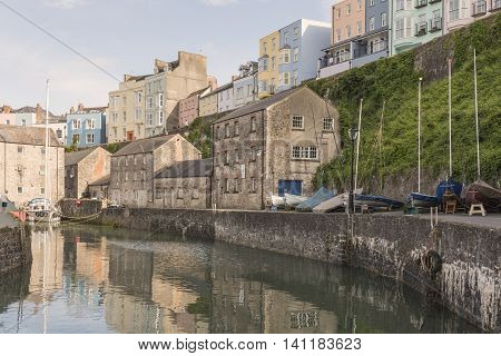 An image of Tenby quayside and the surrounding pastel coloured houses which overlook, shot in evening light at Tenby, Pembrokeshire, South Wales. UK