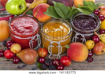 jams of cherries apricots and blueberries with decoration of fruits