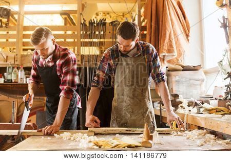 profession, carpentry, woodwork and people concept - carpenters working with saw and wood plank at workshop