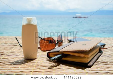 closed notepad, sunglasses, phone with headphones and white tube of cream solar protect on the table against philippine boat on surface tropical sea at sunny day