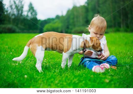 cute baby with a dog in the summer park