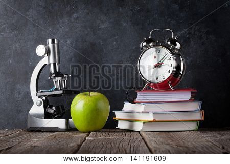 Microscope, alarm clock, books and apple in front of classroom chalk board. Back to school concept with copy space