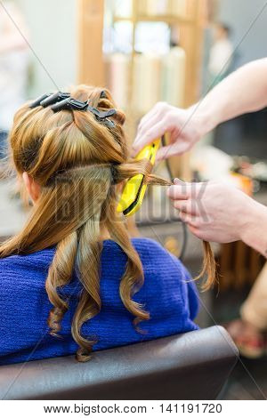 Professional hairdresser using curling iron. Hair curls in salon, people at work