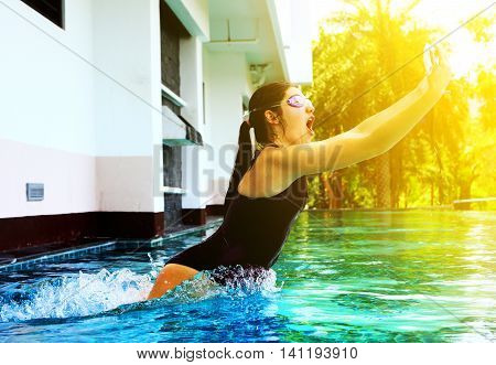 teenager girl in swimming suit jump in water in swimming pool with camera in protective waterproof slipcover cover for underwater photo shooting footage