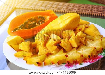 tropical cut fruit plate papaya carambola pineapple mango for dietary light delicious breakfast on the table