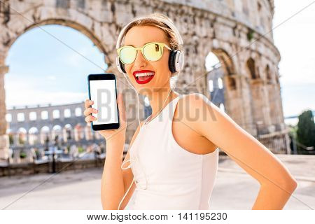 Young sports woman showing smartphone with empty screen standing near the ancient amphitheatre in Pula city.