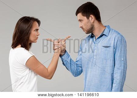 Young beautiful married couple posing, pointing and looking at each other with rancor over grey background.