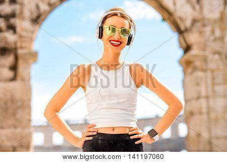 Portrait of a young sports woman with headphones and sunglasses near the ancient amphitheatre in Pula city