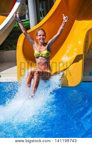 Child girl on water slide at water park show thumb up. Slides with flowing water in water park.