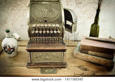 KOLMANSKOP NAMIBIA -JAN 27 2016: Vintage cash register on wooden table in retro style business office. Clay jug and cup out-of-print books and glass bottle with dried flowers. All covered a dust. Filtered image
