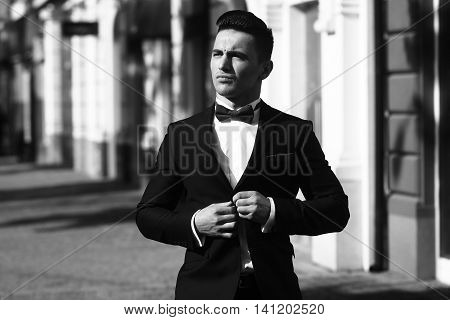 Young Man Unbuttons Suit Coat